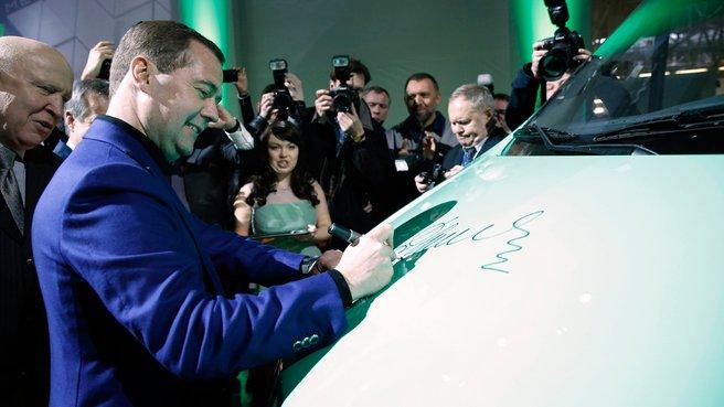 Дмитрий Медведев расписывается на капоте автомобиля «Газель Next»